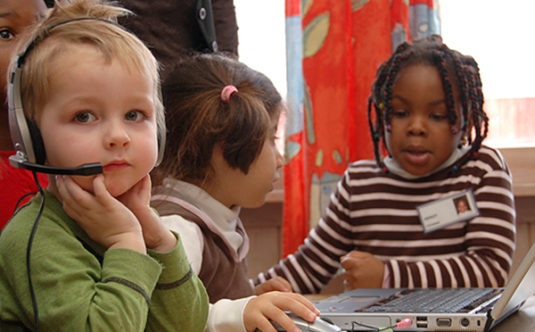 Children sitting at a table. One child is wearing a headset.