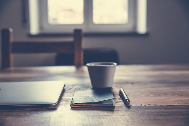 Image of a desk with a laptop, coffee cup, notebook, and pen