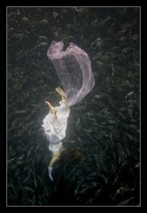 Image of a woman in a pink dress sinking into dark water