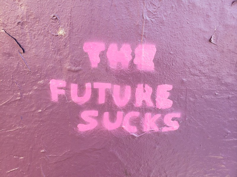 "Photo of ""the future sucks"" spray painted on a pink wall"