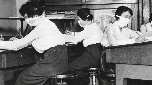Three masked women working at desks, c 1918-1920